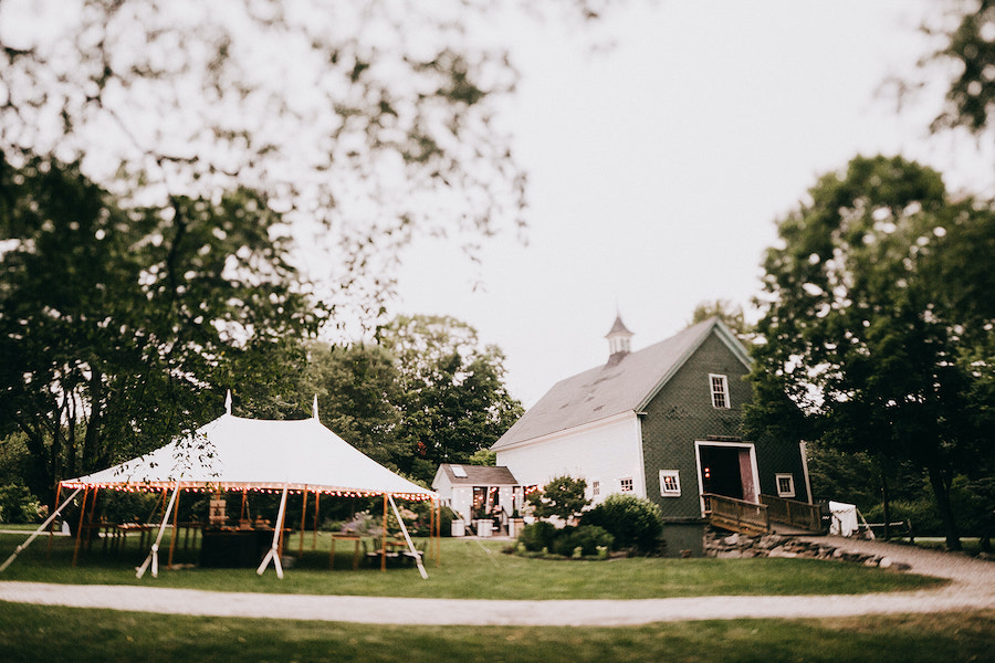 barn and outdoor tent setup at wedding ceremony