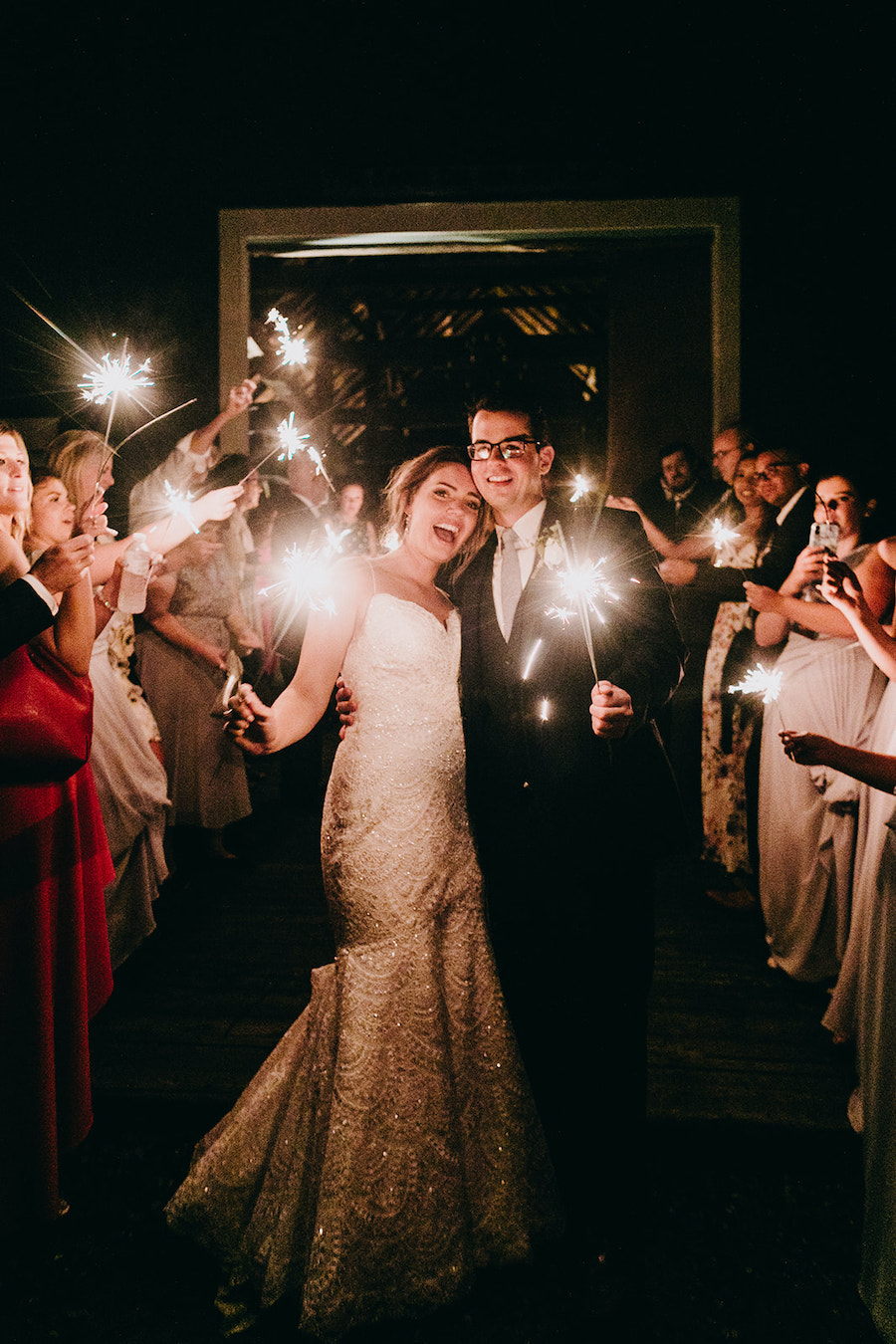 newlywed and guests with sparklers at wedding reception