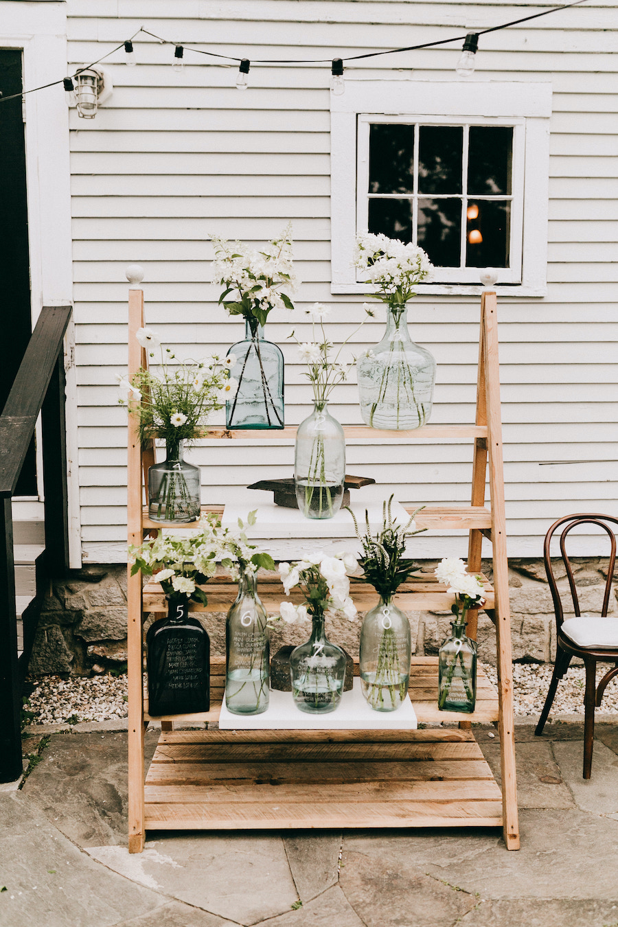 floral vases on wooden ladder display at wedding ceremony