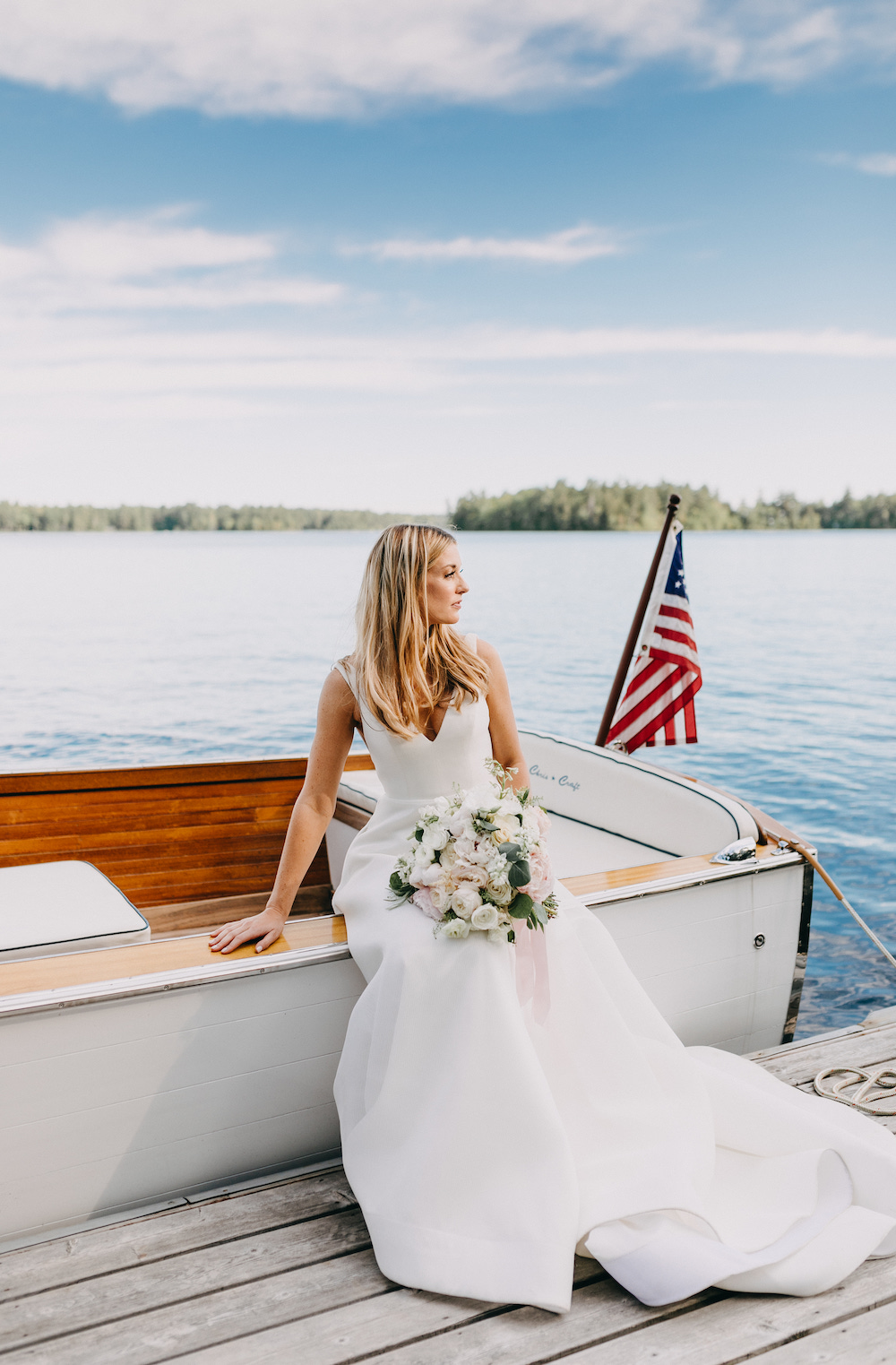 Bride holding bouquet sitting on a dock on the lake.