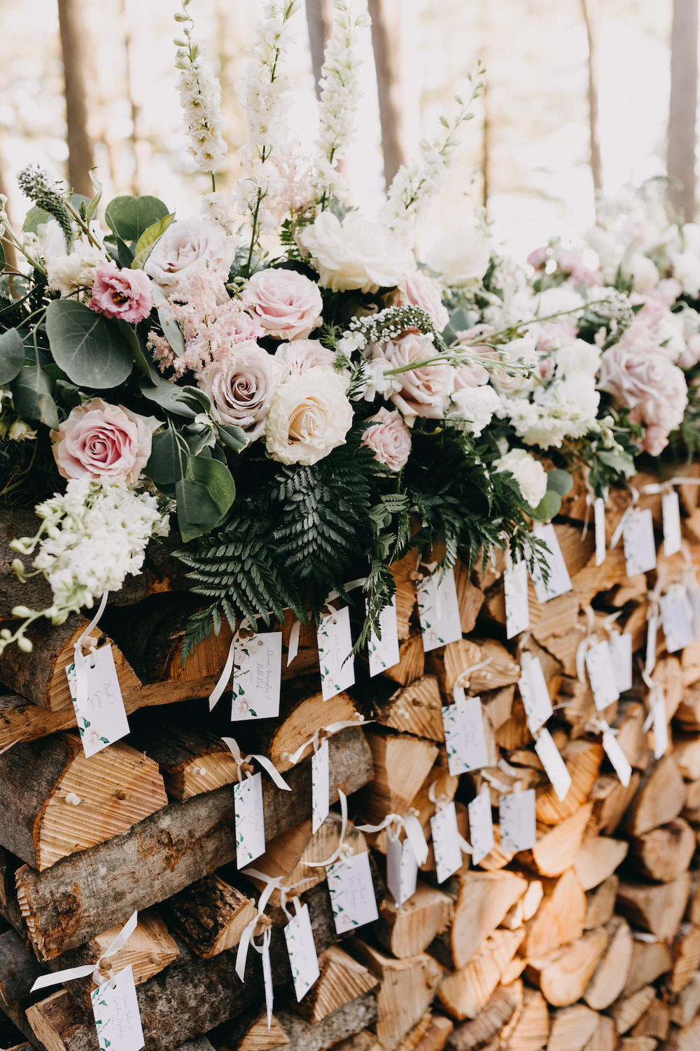 Blush and white florals and escort cards hanging on a wood pile.