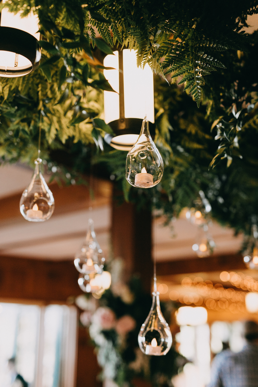 Greenery and hanging glass bulbs hanging above tabletops.