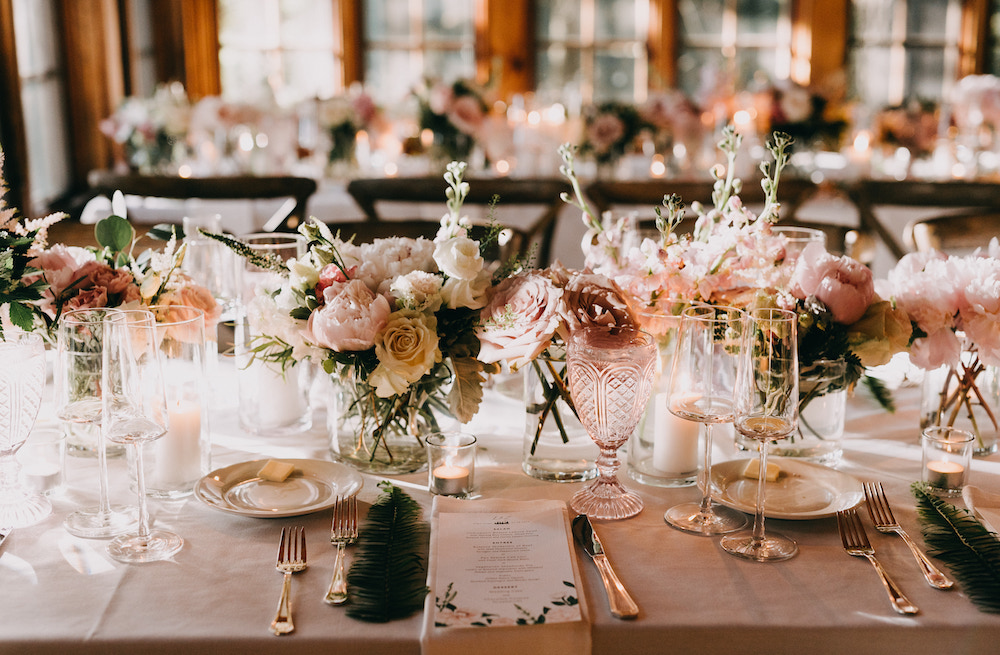 Pink glass goblets and floral centerpieces with blush and white blooms.