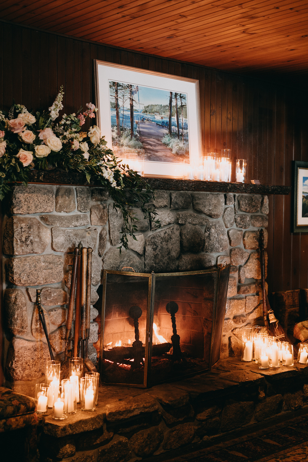 Hearth filled with candlelight and cascading florals.