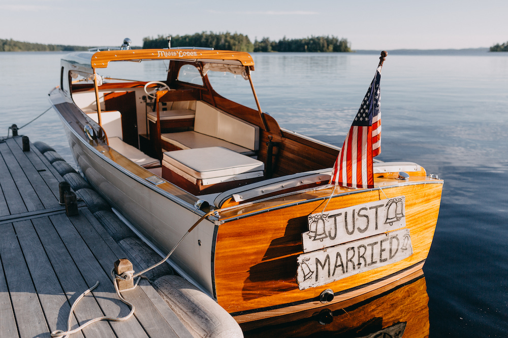 Classic boat with a Just Married sign sitting on the lake.