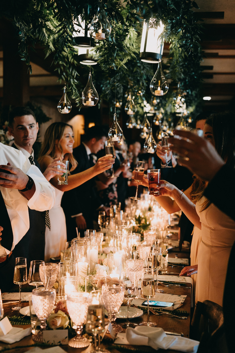Guests cheers beneath hanging greenery and lighting.