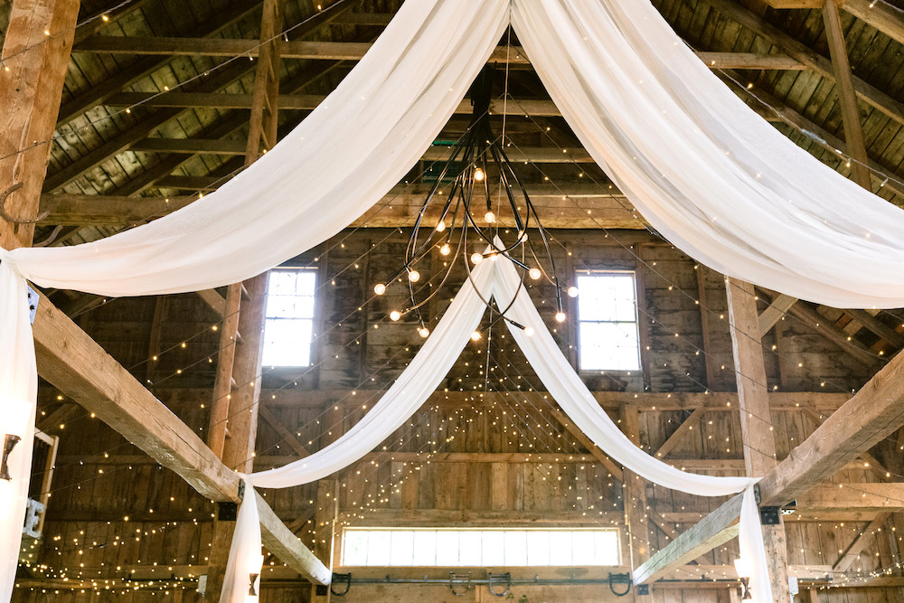 String lights and white fabric draped over the wedding aisle.
