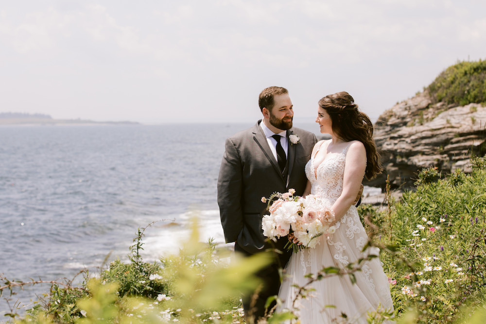A portrait of the bride and groom on a hillside overlooking the coastline.