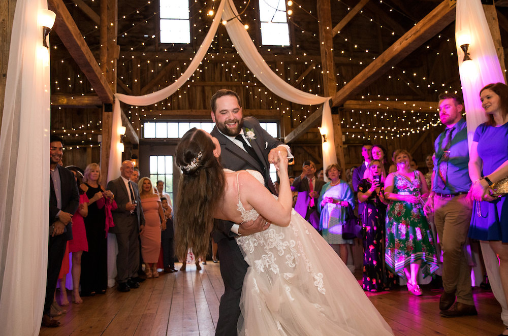 Newlyweds dip during their first dance on the at their pastel hued wedding.