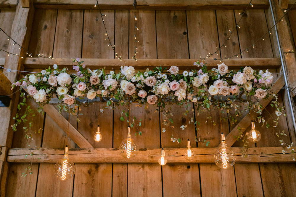 A suspended floral chandelier with bulbs hanging from it