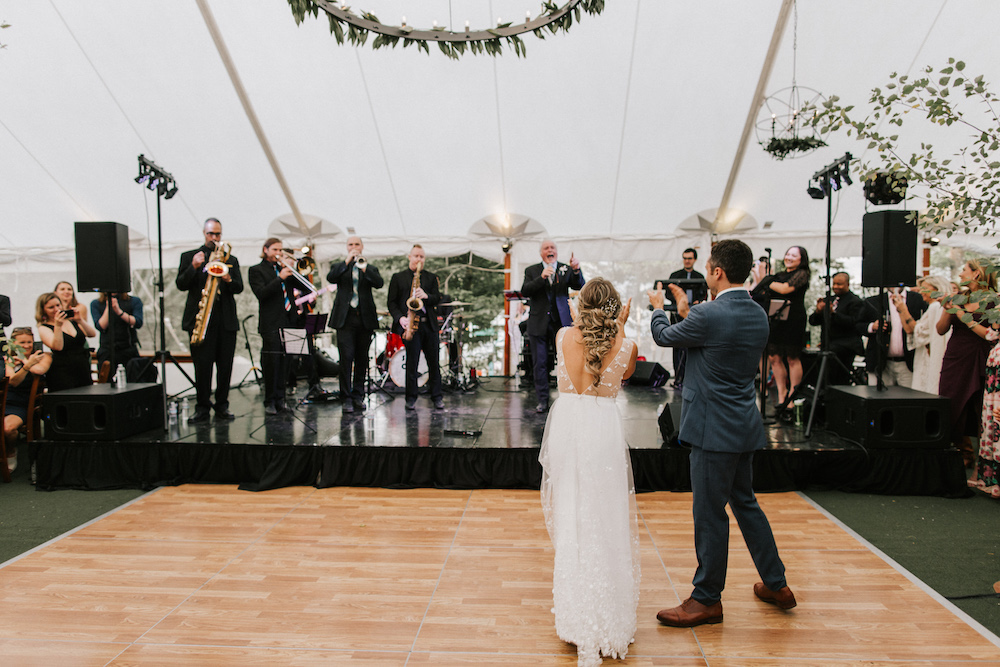 Bride and groom clap for live band playing on stage.