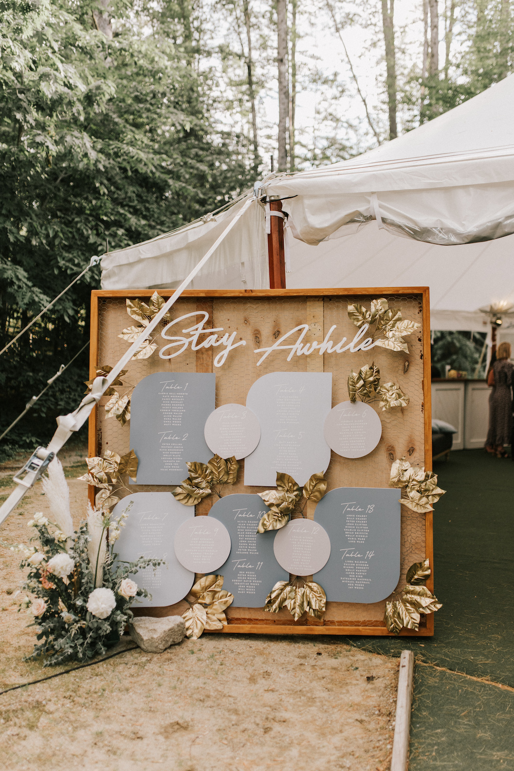 A boho seating sign saying Stay Awhile with florals and gold leaf details