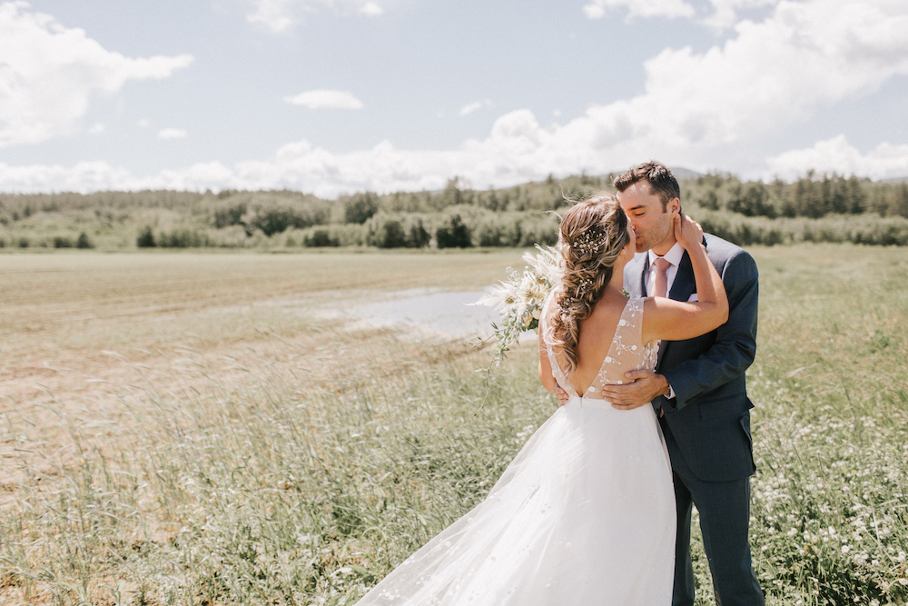 Bride and groom share kiss in lush green field.