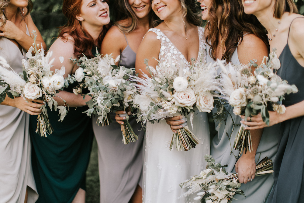 Bride and bridesmaids smiling while holding boho floral bouquets