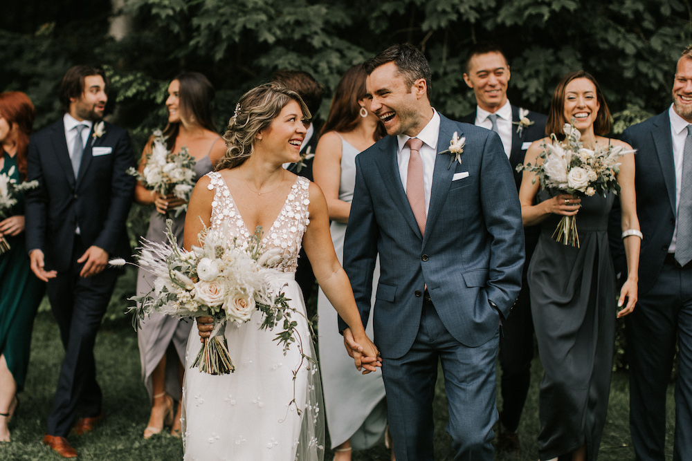 Bride and groom smiling with wedding party trailing behind them