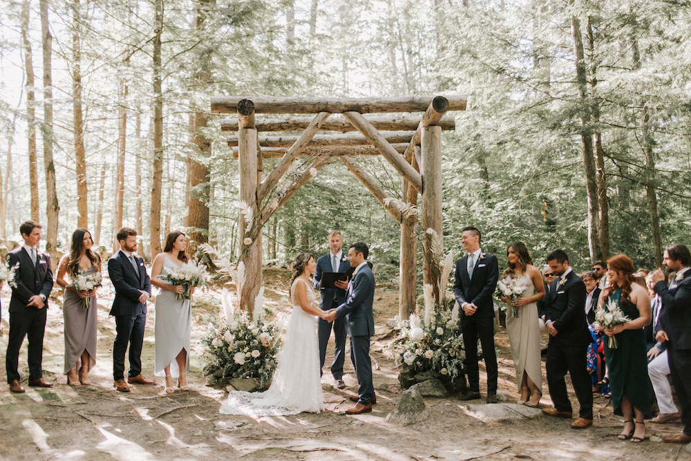 Wedding ceremony beneath wooden pergola and towering forest trees