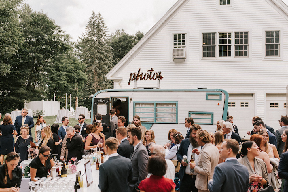 Cocktail hour outside a white barn with a vintage photo booth