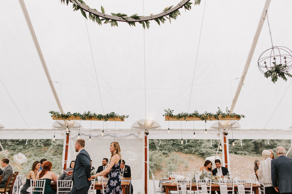 Custom griffin griffin lighting installation above tabletops of tented wedding