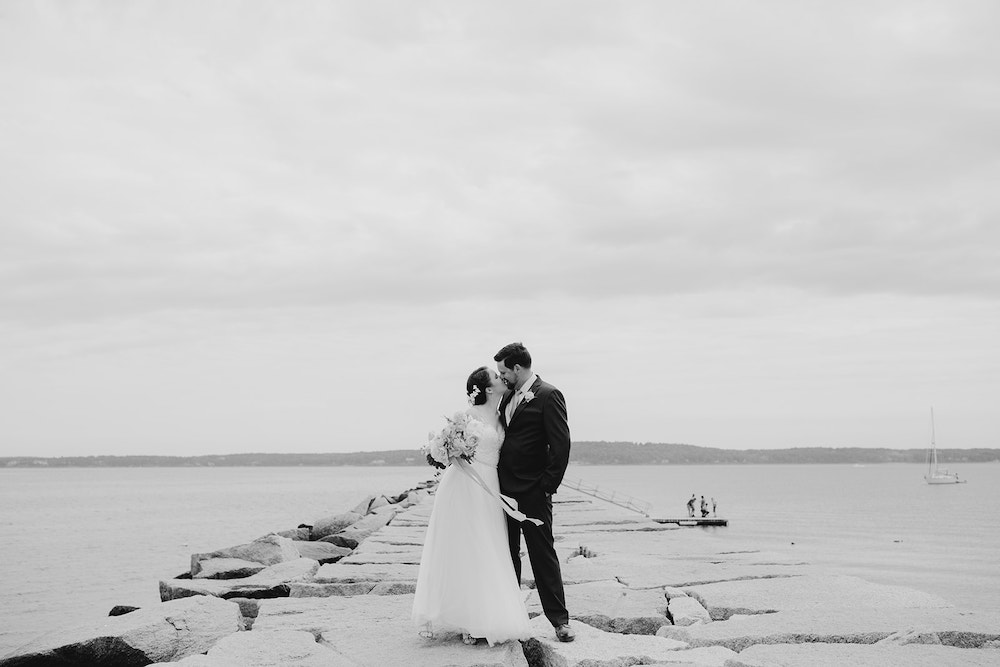 Black and white photo of bride and groom on the lake.