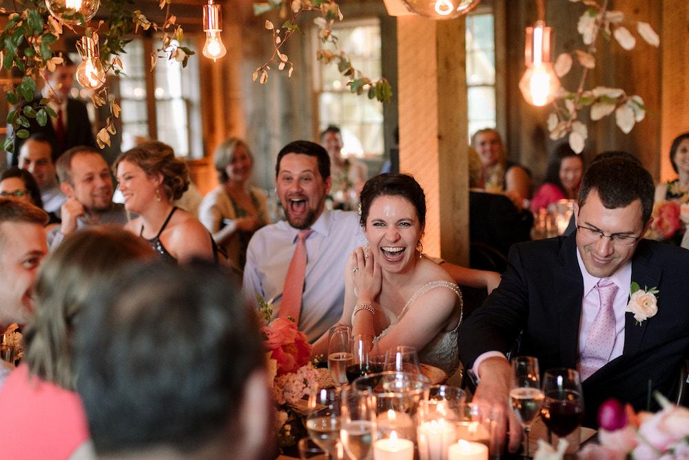 Bride and groom enjoying wedding reception beneath beautiful lighting.
