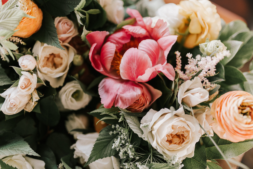 Up close shot of blush, pink, and peach roses and greenery