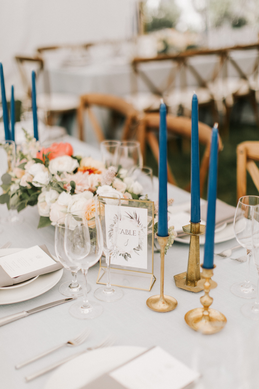 Blue taper candles in gold candle sticks on tabletops of House Island reception