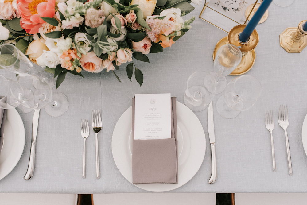 Soft grey linen tabletops with silver flatware, white china, and colorful floral centerpieces