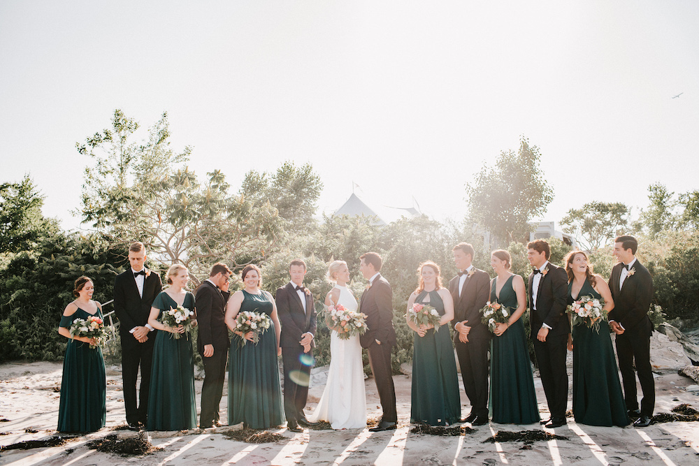 Newlyweds surrounded by their bridesmaids in emerald green and groomsmen in black tuxes