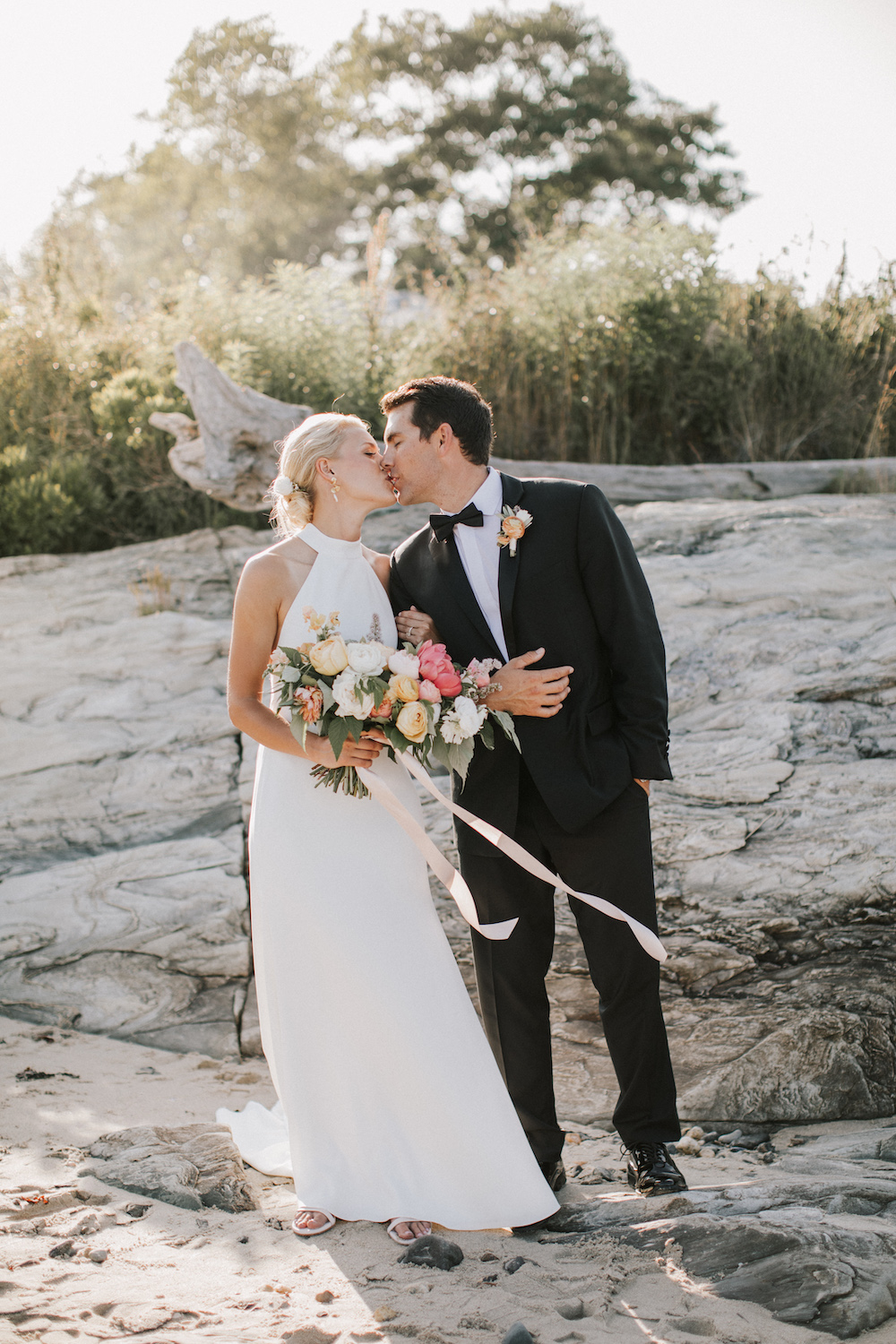 Bride and groom kiss on the shore of House Island