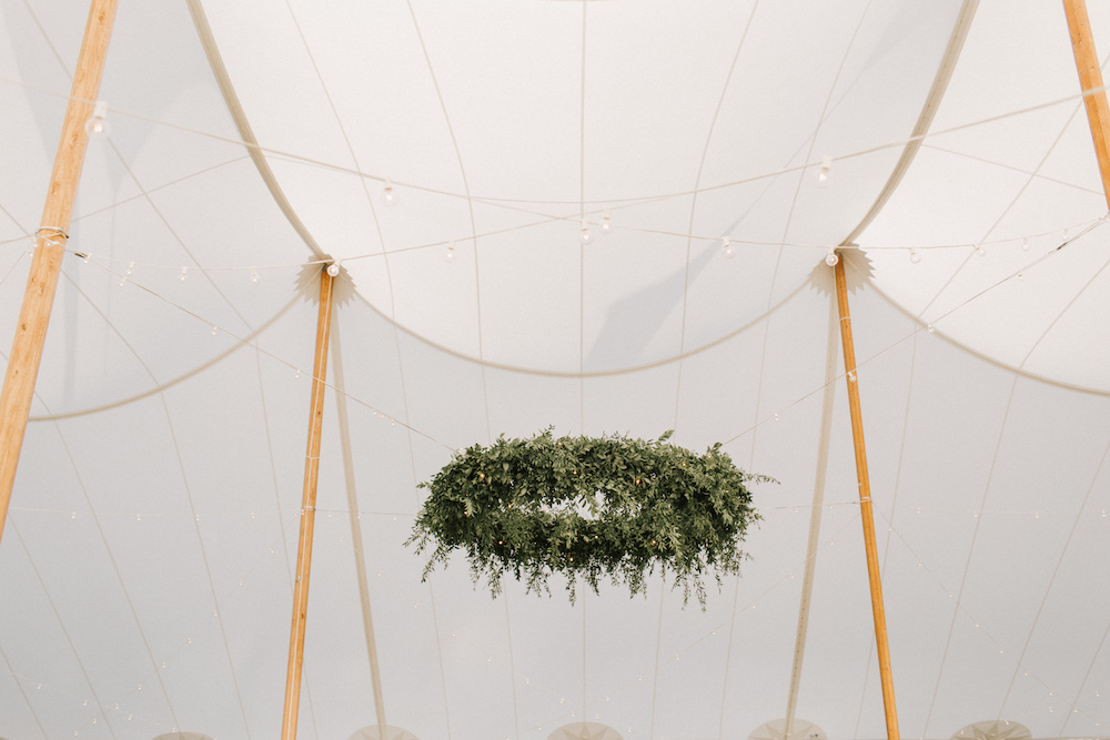 Circular greenery lighting structure hangs from center of reception tent