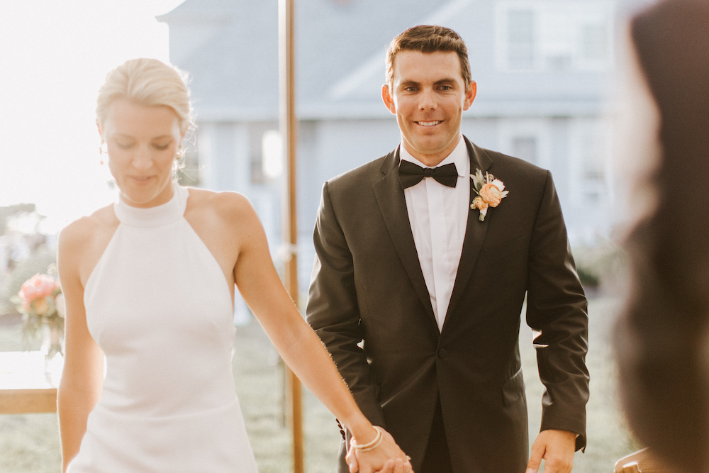 Bride and groom walk to dance floor hand in hand with sun shining behind them