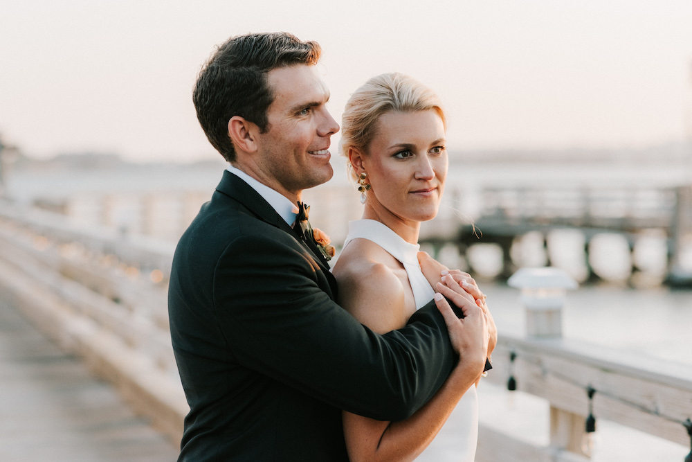 Bride and groom embrace on the docks on House Island at sunset.