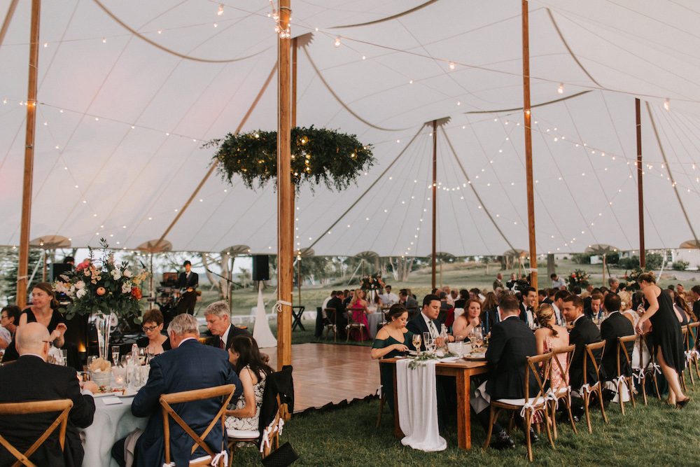 Strings of light illuminate tented Casco Bay wedding reception