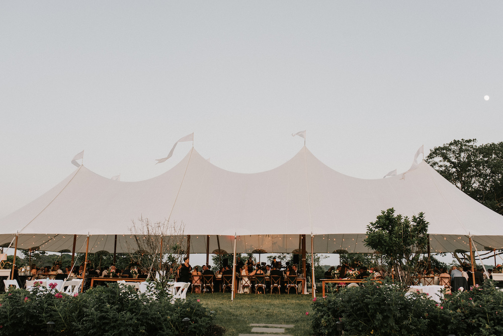 Tented wedding reception on House Island at dusk