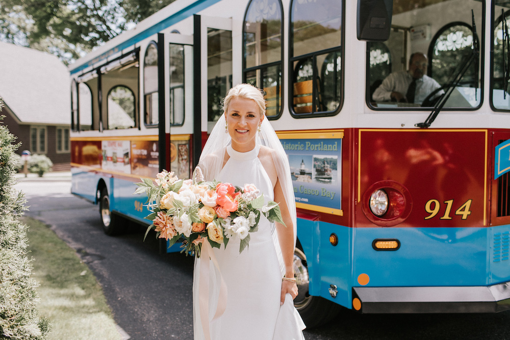 Bride holding her colorful floral bouquet in front of trolly