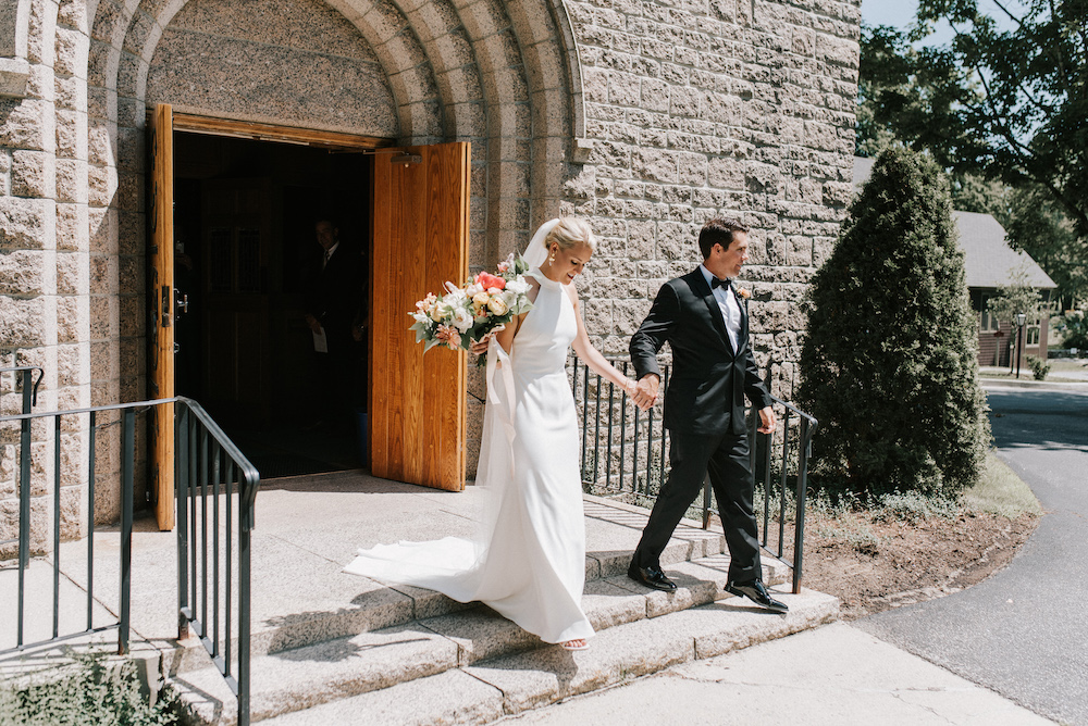 Bride and groom stepping out of church hand in hand as newlyweds
