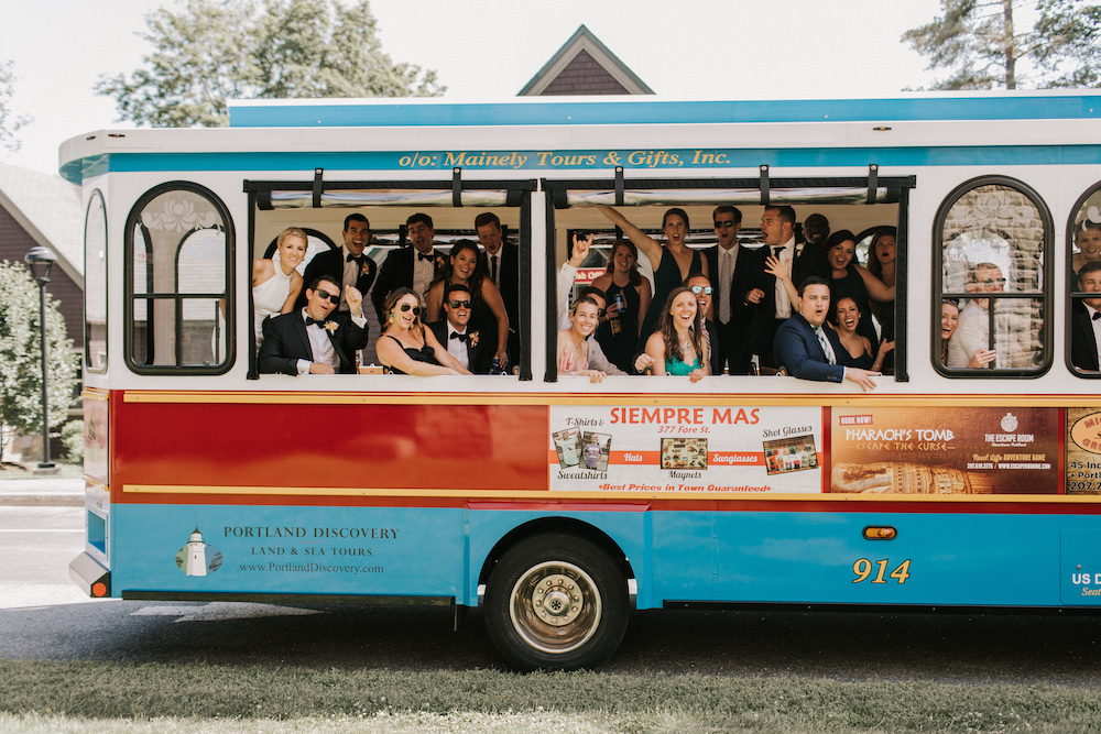 Newlyweds and their wedding party wave from trolly leaving wedding ceremony