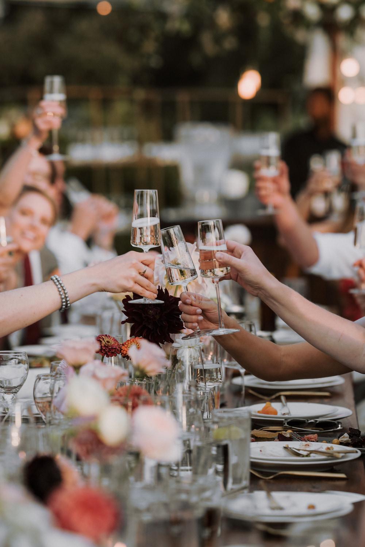 Guests clink champagne glasses together over tableotp.