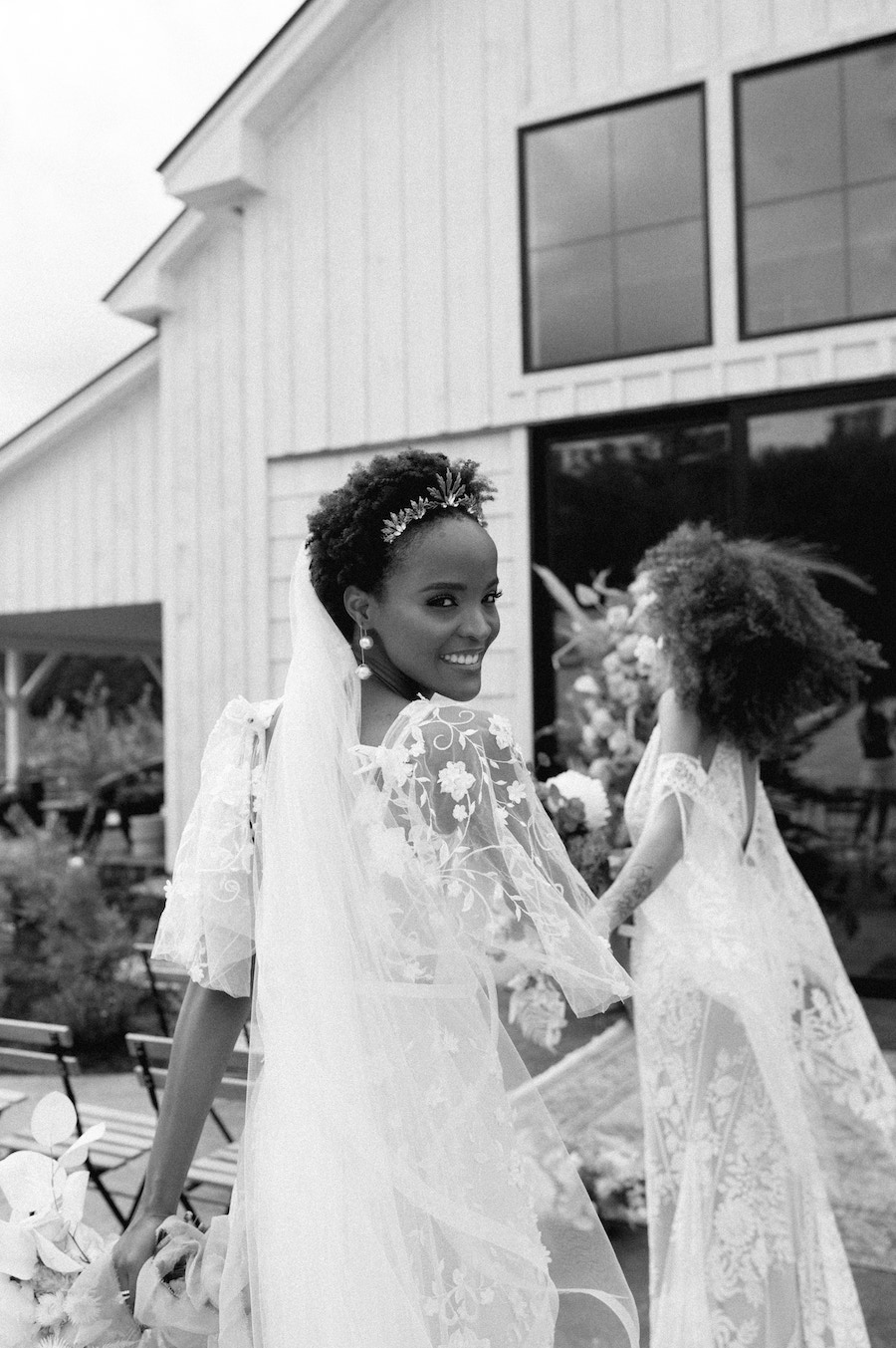 Black and white shot of bride looking back while holding hands with her bride.