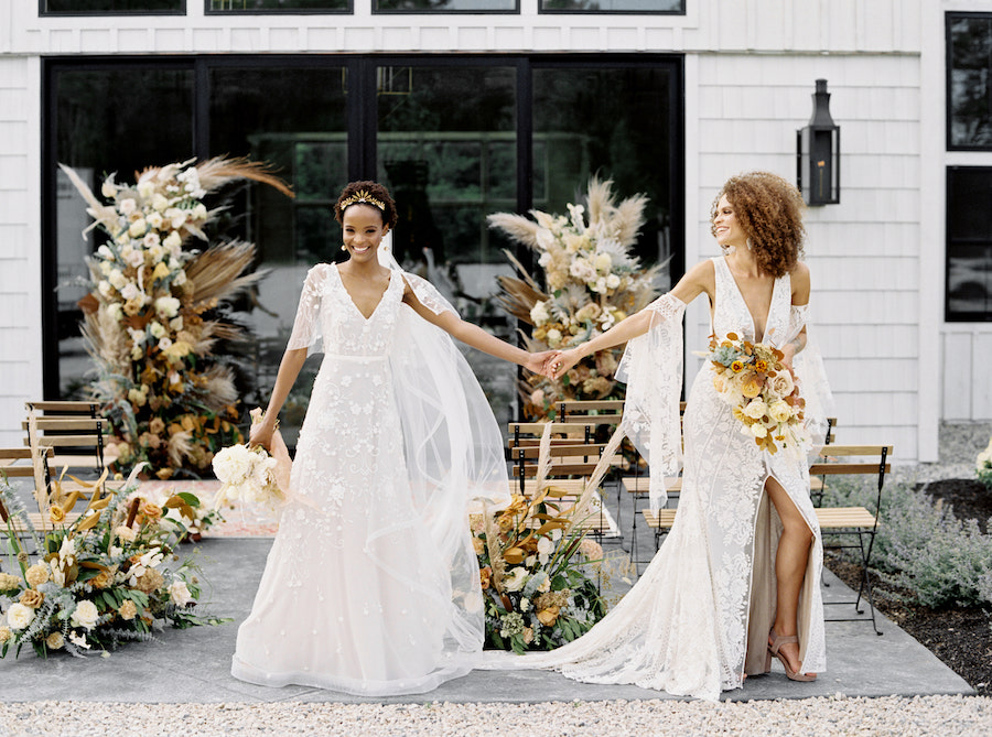 Two brides hold hands in front of ethereal wedding ceremony site.