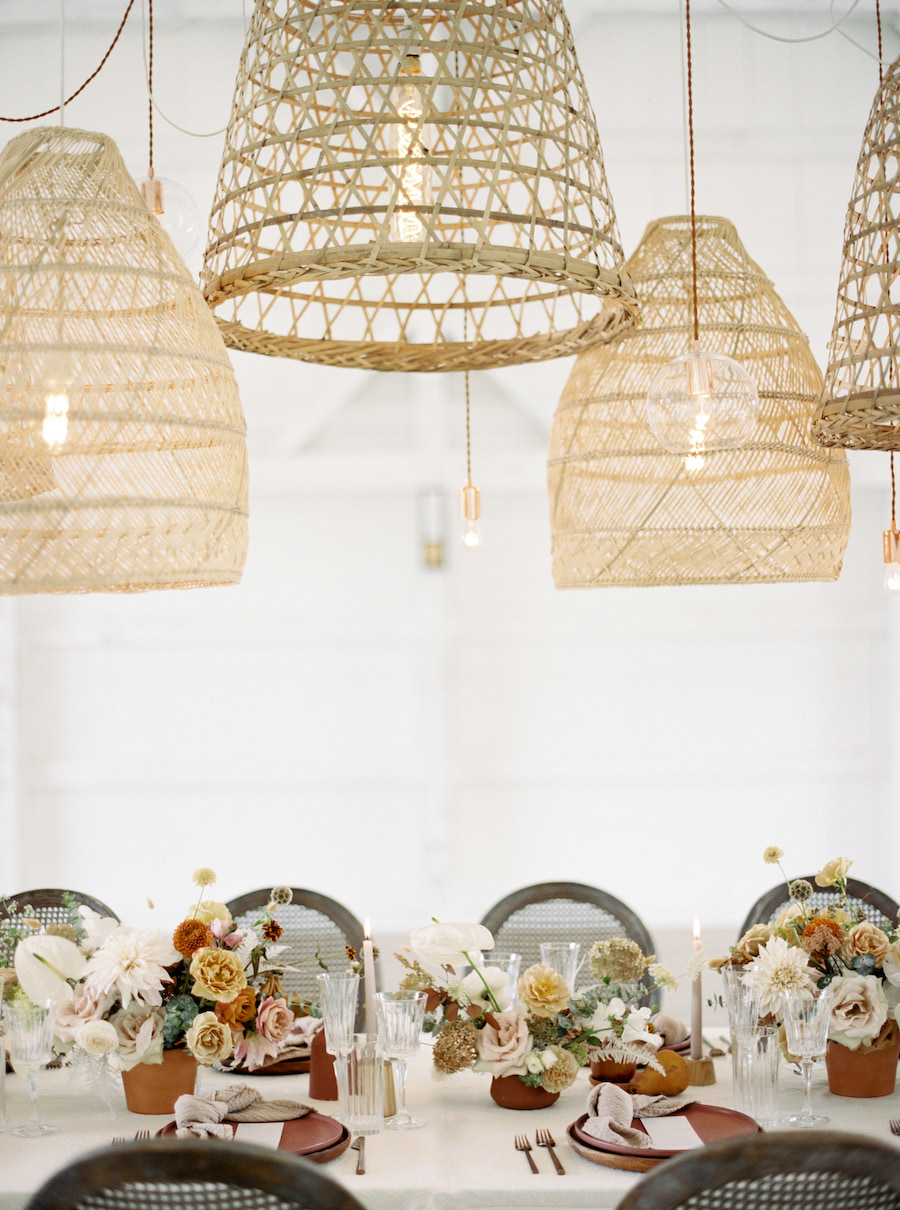 Bohemian lighting fixtures hung over tabletop filled with florals and stoneware.