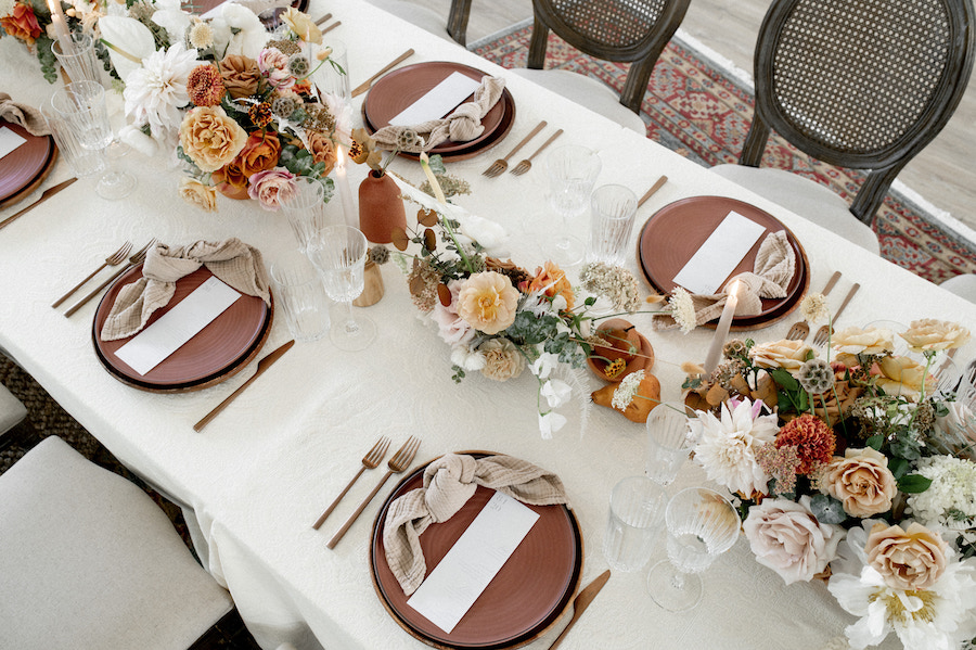 A look down at details of tabletop with stoneware, linen napkins, and peachy florals.