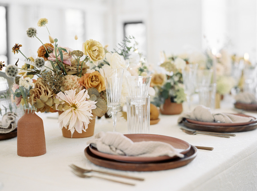 Close up of place setting on tabletop with neutral tones stoneware, elegant glassware, and florals.