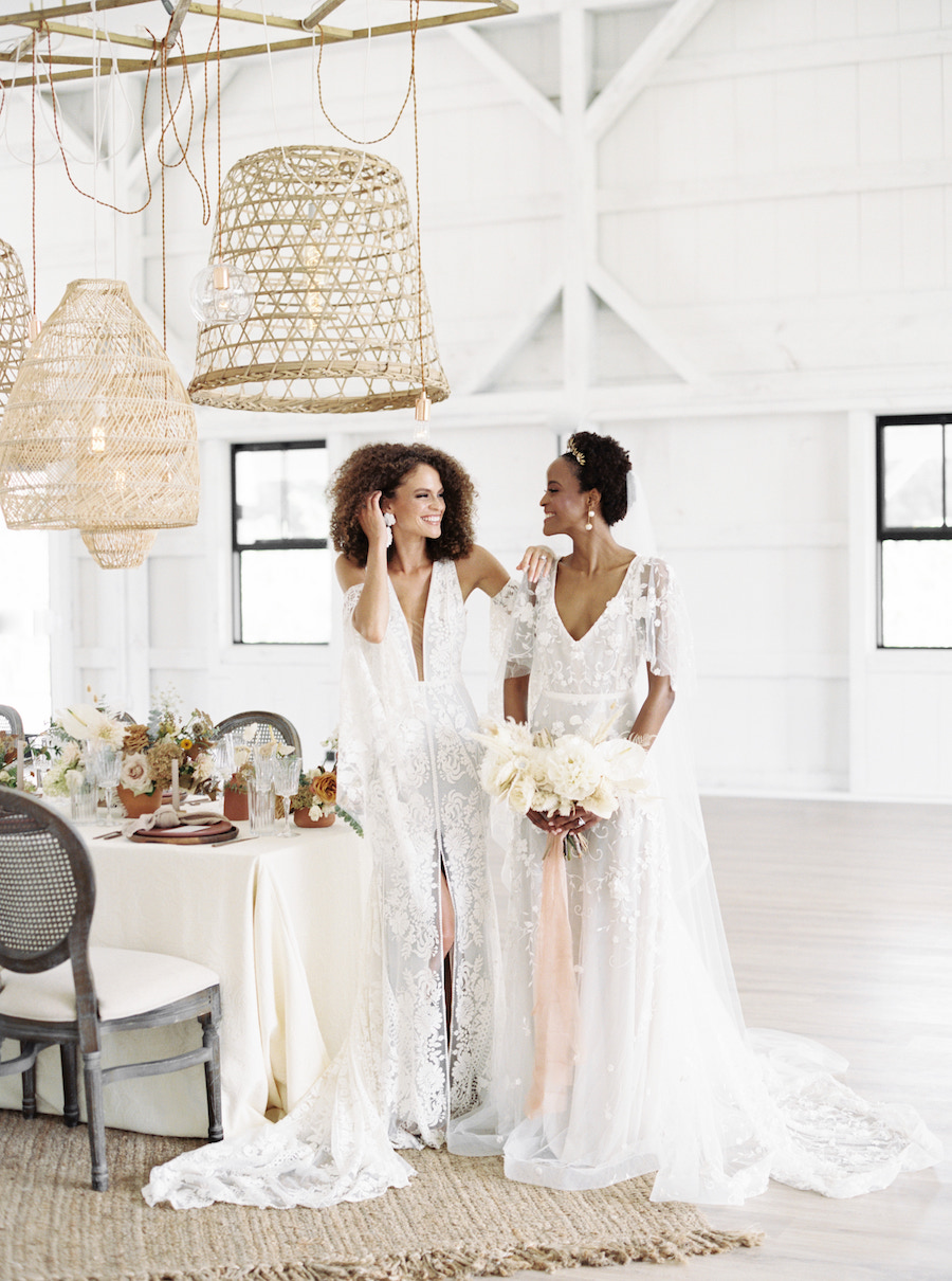 Brides smiling at each other while standing next to ethereal wedding reception table.