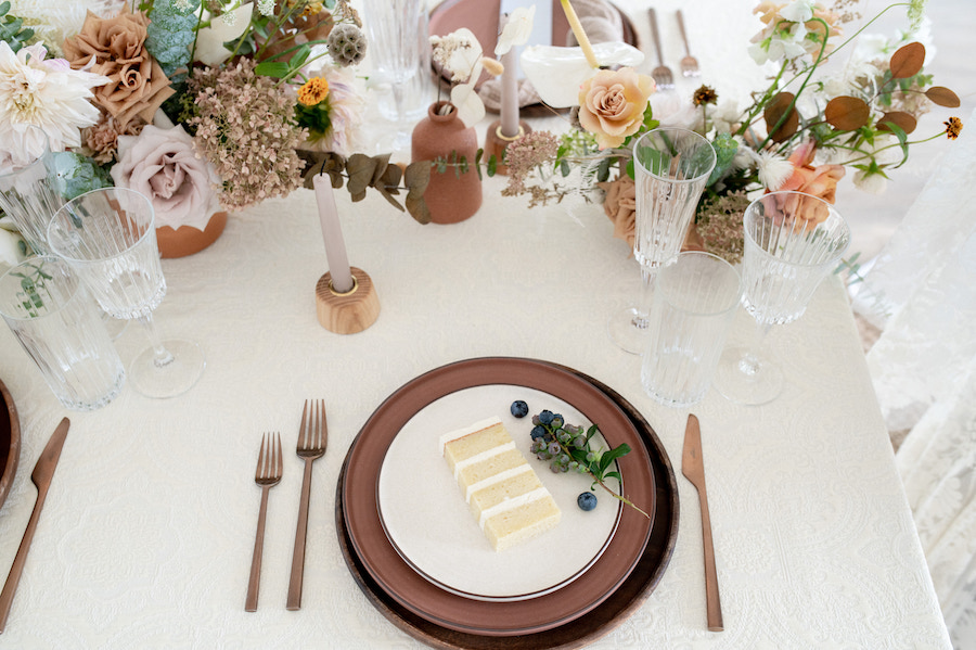 Slice of cake elegantly displayed on place setting.