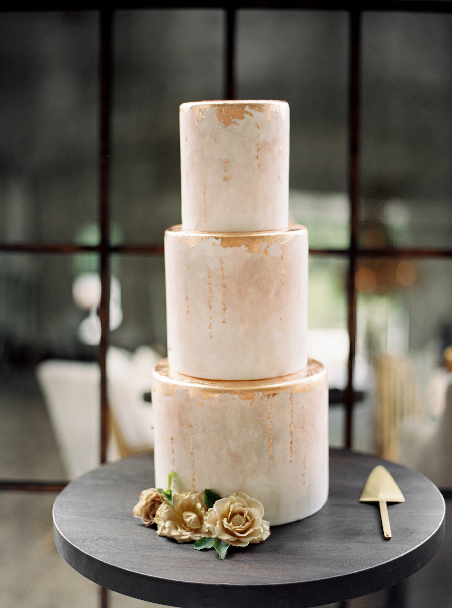 Three tiered modern wedding cake with gold leaf details and three flower buds at the base.