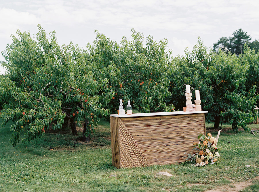 Wooden bar adorned with candles and florals sits in front of orchard trees.