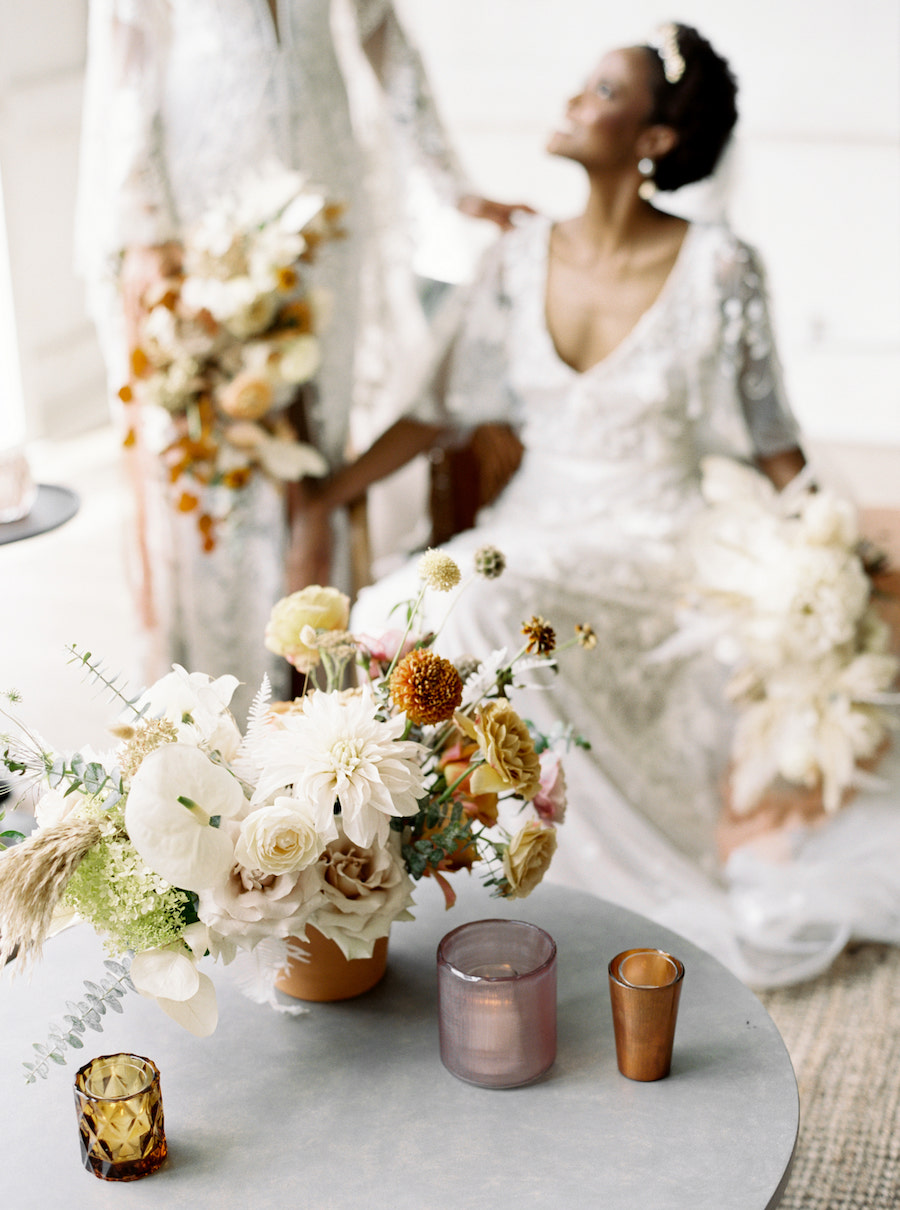 Ivory and peachy floral centerpiece sits on coffee table with brides looking at each other in the background.