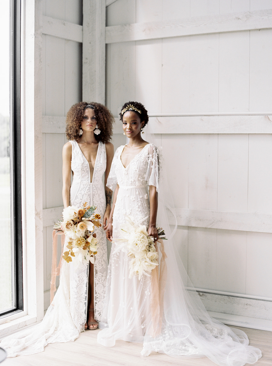 Two brides standing regal with wildflower bouquets against white backdrop.