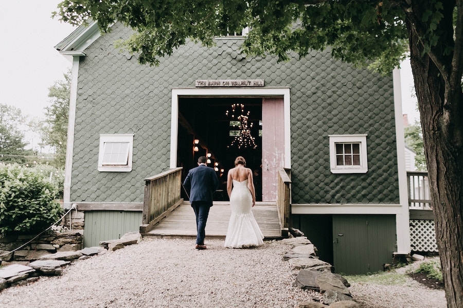 Bride and groom entering their Maine barn reception.